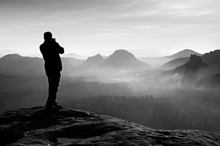 Photographer takes photos with big camera on peak of rock. Dreamy misty landscape, hot Sun above