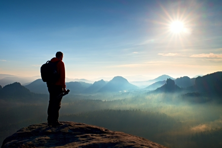 people in action: Tall photographer with heavy backpack and tripod in hands stand on rocky view point and watching down to deep misty valley bellow Stock Photo