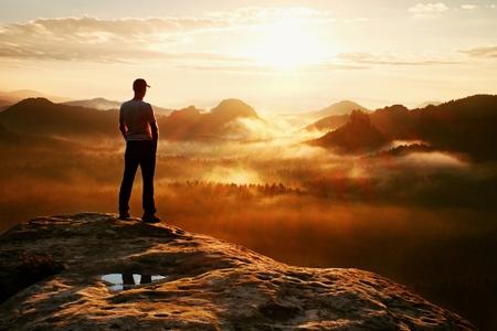 赤キャップでハイカーは自然の奇跡ロック帝国公園と日美しい瞬間に霧と霧の朝渓谷を見て砂岩の岩のピークの上に立ちます。