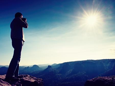 photoblog: Professional photographer takes photos with big camera on peak of rock. Dreamy misty landscape, hot Sun above Stock Photo