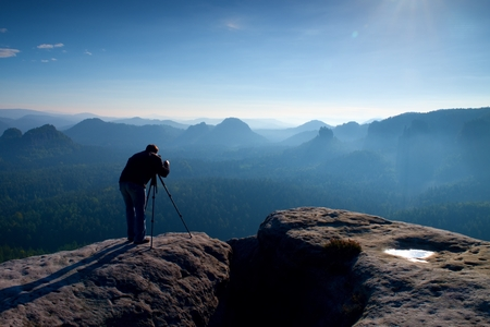 documenting: Professional on cliff. Nature photographer takes photos with mirror camera on peak of rock. Dreamy fogy landscape, spring orange pink misty sunrise in a beautiful valley below.