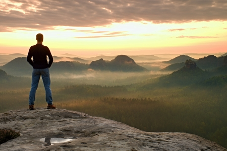 empires: Hiker is standing on the peak of sandstone rock in rock empires park and watching over the misty and foggy morning valley to Sun. Beautiful moment the miracle of nature