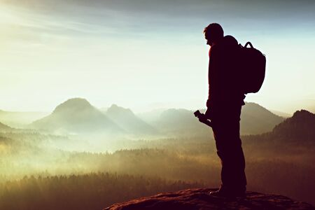 hobbyist: Tall adult  photographer think about picture at sunset in the misty mountains