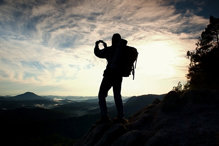 valley below: Tourist with backpack takes photos with smart phone on the rocky peak. Dreamy fogy valley below Stock Photo
