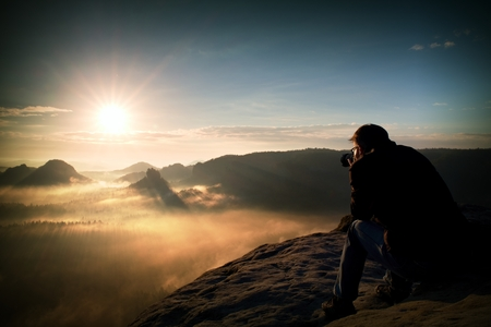 great job: Tourist sit on the peak of sandstone rock and watching into colorful mist and fog in morning valley.