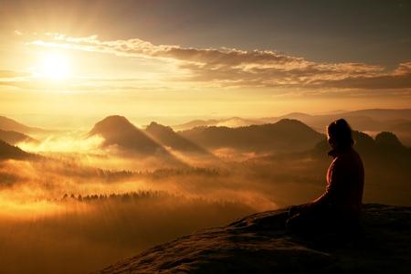 美しい若い女性観光客は砂岩の岩の鋭い角の夜明けをお楽しみくださいし、太陽の谷を見守る。