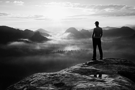 saxon: Hiker in red cap stand on the peak of sandstone rock in rock empires park and watching over the misty and foggy morning valley to Sun. Beautiful moment the miracle of nature