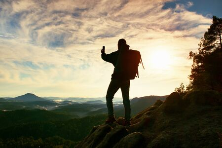 rocky peak: Tourist with backpack takes photos with smart phone on the rocky peak. Dreamy fogy valley below Stock Photo