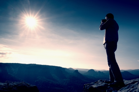 Professional photographer takes photos with big camera on peak of rock. Dreamy misty landscape, hot Sun above Фото со стока