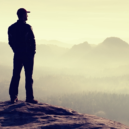 empires: Alone hiker in red cap stand on the peak of sandstone rock in rock empires park and watch into sun Stock Photo