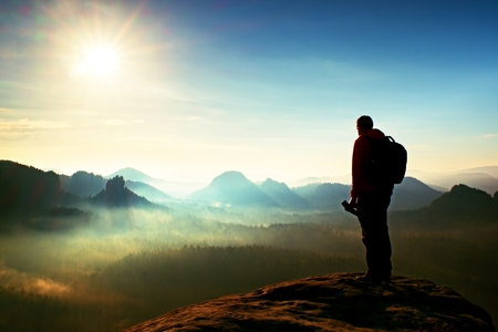 think about: Tall adult  photographer think about picture at sunset in the misty mountains