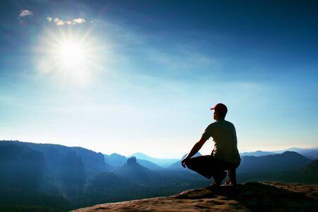 en cuclillas: Runner in red cap and  in dark sportswear in squatting position on a rock in heather bushes, enjoy the scenery