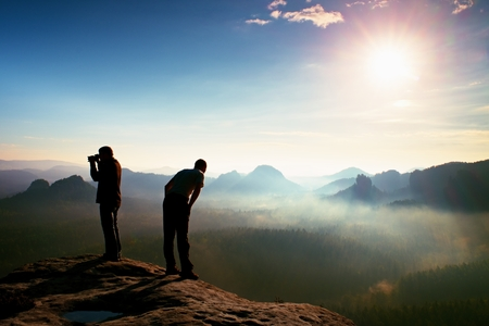 documenting: Hiker and photo enthusiast stay on cliff and thinking. Dreamy fogy landscape, blue misty sunrise in a beautiful valley below