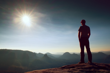 saxon: Alone hiker in red cap stand on the peak of sandstone rock in rock empires park and watching over the misty and foggy morning valley to Sun. Beautiful moment the miracle of nature Stock Photo