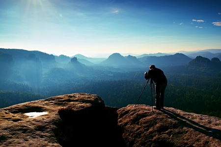 valley below: Professional on cliff. Nature photographer takes photos with mirror camera on peak of rock. Dreamy fogy landscape, spring orange pink misty sunrise in a beautiful valley below.