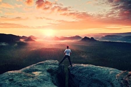 Crazy jumping hiker in black celebrate triumph between two rocky peaks. Wonderful daybreak. Banco de Imagens