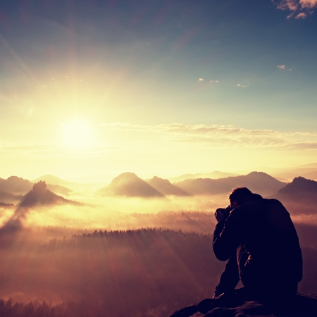valley below: Happy photo enthusiast is  enjoying fantastic miracle of nature on cliff on rock. Dreamy fogy landscape, blue misty sunrise in a beautiful valley below Stock Photo