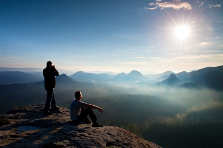 valley below: Hiker and photo enthusiast stay with tripod on cliff and thinking. Dreamy fogy landscape, blue misty sunrise in a beautiful valley below Stock Photo