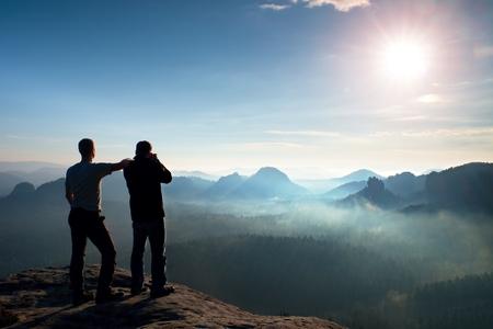 ハイカーと写真愛好家は、崖と思考に滞在します。美しい渓谷の下で夢のような濃霧発生風景、青い霧日の出