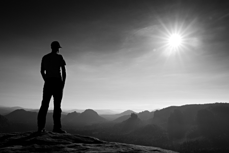 empires: Alone hiker in red cap stand on the peak of sandstone rock in rock empires park and watching over the misty and foggy mornings Sun Valley Beautiful moment the miracle of nature