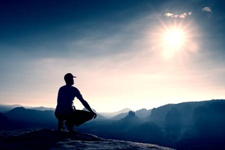 horizonte: Corredor en la gorra roja y en ropa deportiva oscura en la posición en cuclillas sobre una roca en matorrales de brezo, disfrutar del paisaje