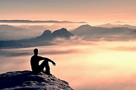 rocky peak: Hiker in black on the rocky peak. Wonderful daybreak in mountains, heavy mist in deep valley. Man sit on the rock.