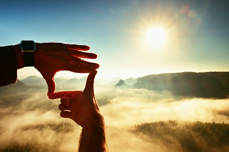 Close up of hands making frame gesture. Blue misty valley bellow rocky peak. Sunny spring daybreak in mountains.