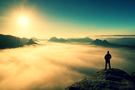 El hombre se coloca en la cima de la roca arenisca en el parque nacional de Suiza, Sajonia y viendo a Sun. Hermoso momento el milagro de la naturaleza
