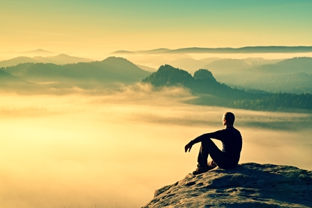 Hiker in black on the rocky peak. Wonderful daybreak in mountains, heavy mist in deep valley. Man sit on the rock.