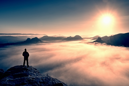 Man stands on the peak of sandstone rock in national park Saxony Switzerland and watching to Sun. Beautiful moment the miracle of nature