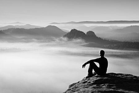 estado del tiempo: Caminante en negro en el pico rocoso. amanecer maravilloso en las monta�as, niebla pesada en el valle profundo. El hombre se sienta en la roca. Foto de archivo