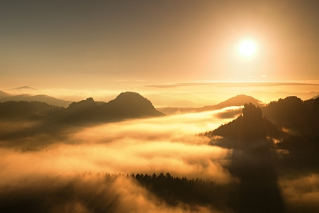 increased: Sunrise in a beautiful mountain of Czech-Saxony Switzerland. Sandstone peaks increased from orange sun rays.