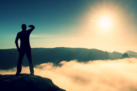 empires: Funny boy on the sharp peak of rock in rock empires park is watching over the misty and foggy morning valley to Sun Stock Photo