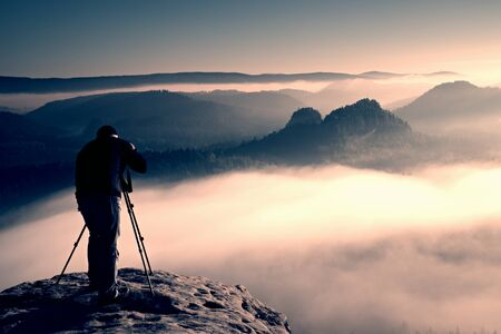documenting: Professional on cliff. Nature photographer Takes photos with mirror camera on the peak of rock. Dreamy fogy landscape, spring orange pink misty sunrise in a beautiful valley below.