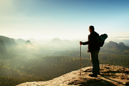 rocky point: Backpacker with eyeglasses and poles in hand. Sunny spring daybreak in rocky mountains. Hiker with big backpack stand on rocky view point above misty valley. Stock Photo