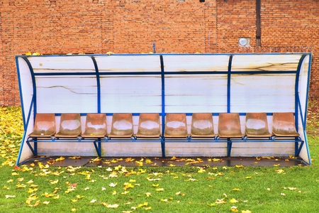 seson: Old plastic seats on outdoor stadium players bench, chairs with worn paint below yellow roof.  Autumn leaves, end of football season. Stock Photo