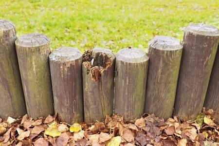 upright row: Broken fence, old wooden stockade, palisade, stony background.