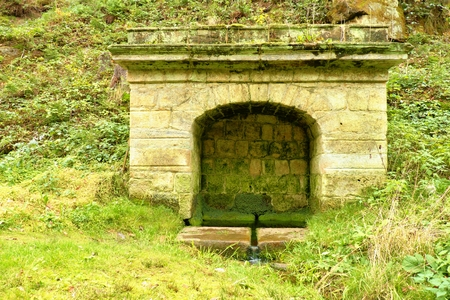 crystal clear: Old Stone rural fountain in the forest with fresh crystal clear water. . Natural drinking water from mountain stream. Stock Photo