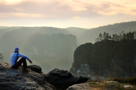 saxon: Moment of loneliness. Man sit on the peak of a rock and watching into colorful mist and fog in forest valley.