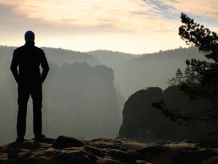 empires: Hiker is standing on the peak of sandstone rock in rock empires park and watching over the misty and foggy mornings Sun Valley Beautiful moment the miracle of nature