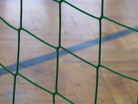 indoor soccer: Detail of yellow blue crossed soccer nets, football in soccer goal net with wooden indoor playground in the background.