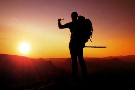 marvellous: Strong man hiker taking photo with smart phone at mountain peak. Marvellous daybreak.