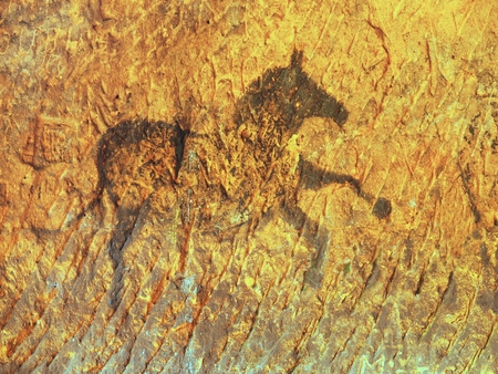 Abstract art children in sandstone cave. Black carbon paint of horses on sandstone wall, copy of prehistoric picture.