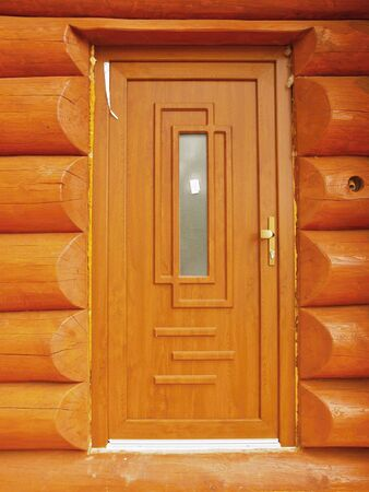 fungicide: Detail of new built door built in wooden beams cabin wall. Painted wood with fungicide light red paint.
