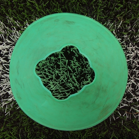 black and white cone: Bright green blue plastic cone on white painted line. Plastic green turf football playground with black rubber grind in core.