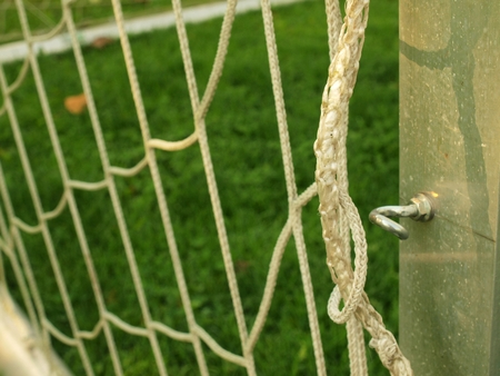 bended: Hang bended soccer nets, soccer football net. Plastic grass and white line painted on football playground in the background Stock Photo