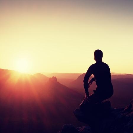 Man tourist sit on peak of mountain. Travel mountain scene. Standard-Bild