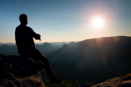 Man tourist sit on peak of mountain. Travel mountain scene. Stock Photo