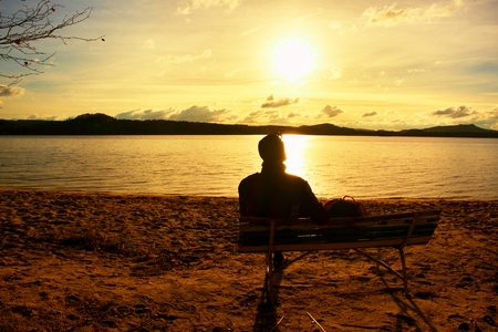 adult footprint: Tired man sit on the old wooden bench on the sea coast. Vintage photo effect