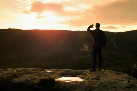 tourist guide: Tourist guide on the way with pole in hand. Hiker with sporty backpack stand on rocky view point above misty valley. Sunny spring daybreak in rocky mountains. Stock Photo